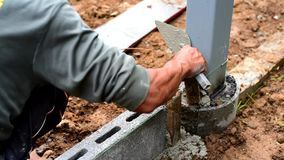 Worker brick the cement wall. In construction site stock footage