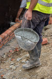 Worker bringing a bucket of mortar Stock Photo