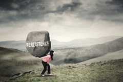 Worker brings boulder with Persistence word Royalty Free Stock Photo