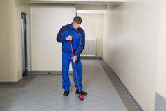 Worker With Broom Cleaning Office Corridor Stock Photo