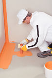 Worker brush applied waterproofing on the floor Royalty Free Stock Image