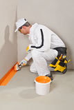 Worker brush waterproofing. Construction worker brush waterproofing around the wall and floor white bucket Royalty Free Stock Image