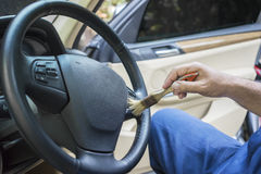 Worker brushing a steering wheel Stock Image