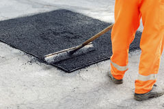 Worker brushing tarmac. Lower body of worker in orange overalls brushing wet tarmac on road surface stock photo