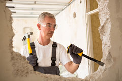 Worker builder demolish wall with tool. Worthy senior man working with hammer and tool while demolish wall Royalty Free Stock Photography