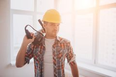 The worker or builder holds a cup of coffee in his hands and looks at the tablet. Against the background of construction. And repair Stock Images