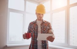 The worker or builder holds a cup of coffee in his hands and looks at the tablet. Against the background of construction. And repair Royalty Free Stock Photo