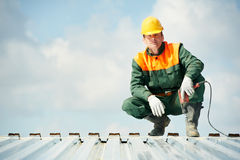 Worker builder roofer at metal profile work. Worker builder with hand drill at metal profile roof installation Royalty Free Stock Photography