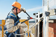 Worker builders at facade tile installation. Worker builder clinching facade construction for big tile on a building with riveting hammer Stock Photos