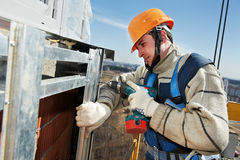 Worker builders at facade tile installation Royalty Free Stock Photo