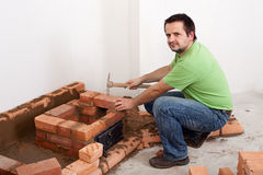 Worker building a brick stove Stock Images