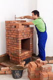 Worker building a brick stove Royalty Free Stock Image