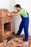 Worker building brick stove or fireplace Royalty Free Stock Image