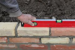 Worker building brick wall, control with level tool. Worker controlling brick wall with level tool, closeup of hand and tool Stock Images