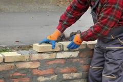 Worker building brick wall. Mason making wall with mortar and bricks, closeup of hands Stock Photos