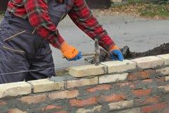 Worker building brick wall using hammer. Mason making wall with mortar and bricks, using hammer tool Royalty Free Stock Photo