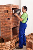 Worker building a masonry heater - trying on an iron and glass d Royalty Free Stock Photos