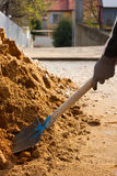 Worker and building sand. Man working with shovel into a pile of building sand Stock Photo