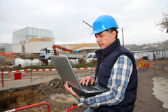 Worker on building site. Engineer on construction site with laptop computer Stock Photo