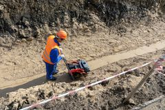 Worker is building a trench sand stone earth stock photos