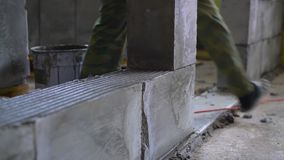 Worker building a wall of aerated concrete blocks stock video footage