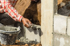Worker building wall on sunny day Stock Photo