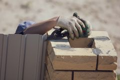 Worker builds brick posts near the gate of the house royalty free stock photos