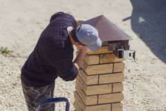 Worker builds brick posts near the gate of the house royalty free stock images