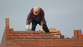 Worker builds wall of bricks. builder on building making bricklaying. builder at the construction site makes brickwork. Brick construction site building stock footage