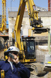 Worker and bulldozer, construction. Worker, building worker with large bulldozer, excavator in background Royalty Free Stock Photos