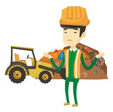 Worker and bulldozer at rubbish dump. Upset asian worker of rubbish dump. Worker of rubbish dump standing with spread arms. Man standing on the background of Royalty Free Stock Images