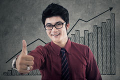 Worker with business graph shows thumb up Royalty Free Stock Images