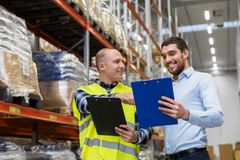 Worker and businessman with clipboard at warehouse. Wholesale, logistic business and people concept - manual worker and businessman with clipboards at warehouse Stock Photo