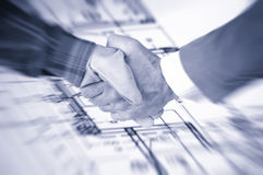 Worker and businessman shaking hands over house renovation plans stock photography