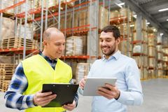 Worker and businessman with tablet pc at warehouse. Wholesale, logistic business and people concept - warehouse worker and businessman with clipboard and tablet Royalty Free Stock Images