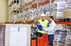 Worker and businessmen with clipboard at warehouse Stock Photos