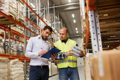 Worker and businessmen with clipboard at warehouse Stock Image
