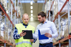 Worker and businessmen with clipboard at warehouse Royalty Free Stock Image