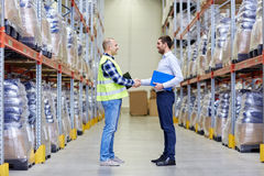 Worker and businessmen with clipboard at warehouse Stock Photography