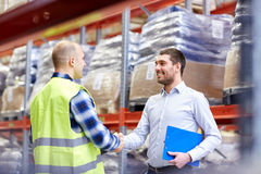 Worker and businessmen with clipboard at warehouse Royalty Free Stock Photos