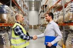 Worker and businessmen with clipboard at warehouse Royalty Free Stock Photography