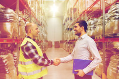 Worker and businessmen with clipboard at warehouse Royalty Free Stock Photo