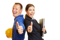 Worker and businesswoman holding their thumbs up. Happy worker and cheering businesswoman holding together their thumbs up Royalty Free Stock Photography