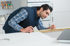 Worker calculating measures on kitchens construction Royalty Free Stock Photography