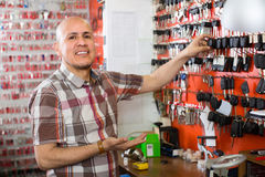 Worker with car keys in locksmith. Smiling mature professional workman with assortment of car keys in locksmith stock image