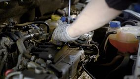 Worker of car repair shop is twisting bolts of small energy unite inside an automobile, using wrench. Close-up of hands stock footage