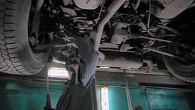 Worker of car-service is checking backlash in the suspension of automobile, he is standing under car, raised on a lift. Control of vehicles stock footage
