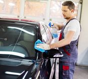 Worker on a car wash. Cleaning car with a spray Stock Photo
