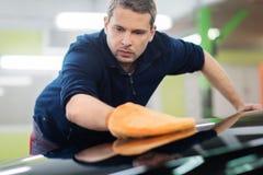 Worker on a car wash. Man worker polishing car on a car wash Stock Image