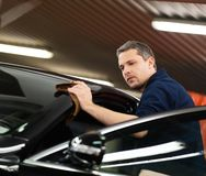 Worker on a car wash. Man worker polishing car on a car wash Stock Images